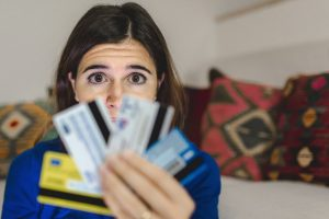 Distressed woman holding several credit cards