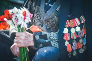 grandpa veteran, wears a jacket adorned with military medals and pins, he wears a beaten up sweater underneath and holds flowers in an old wrinkled hand.